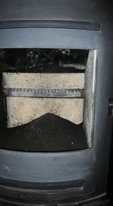 A log burner sealed and being swept.